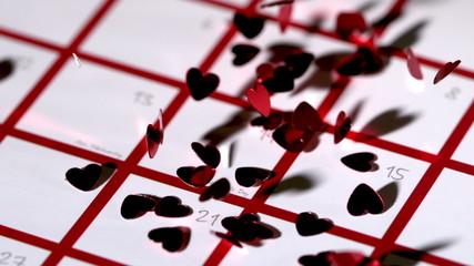 Dark red heart confetti dropping on calendar