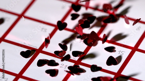 Dark red heart confetti dropping on calendar