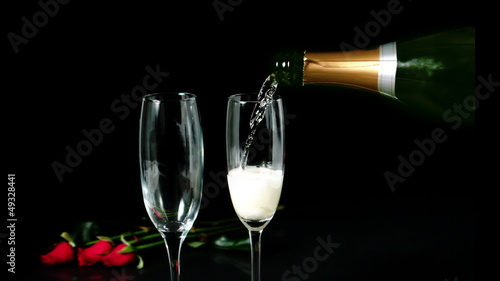 Champagne pouring on a flute with roses behind it