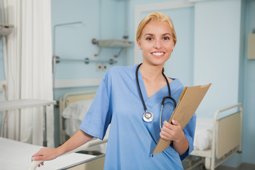 Nurse smiling while holding a folder