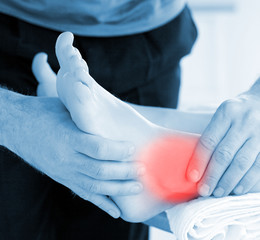 Physiotherapist touching patients highlighted ankle