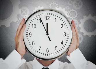 Businessman hiding his face with white clock