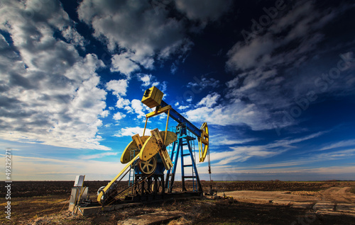 Operating oil well profiled on dramatic cloudy sky - 49329271