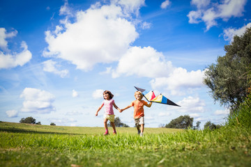 Brother and sister holding hands and playing with a kite