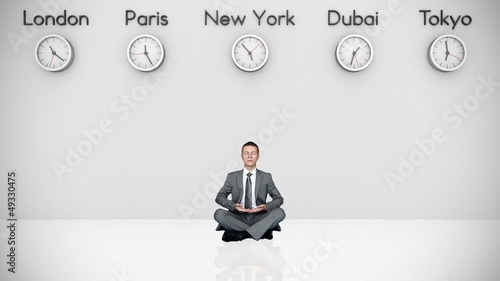 Businessman Meditating with World Clocks on Background