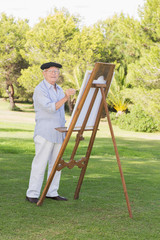 Portrait of smiling man painting in park