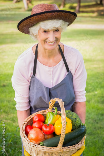 Smiling elderly woman carrying basket of vegetables