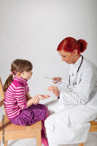 Die Kinderärztin gibt ihrer Patientin eine Tablette