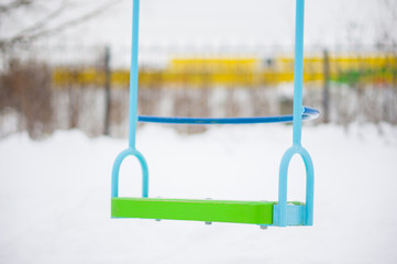 Baby swings on winter playground