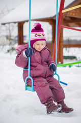 Adorable girl swings on winter snowed playground
