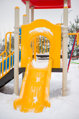 Play construction with baby slide on winter playground