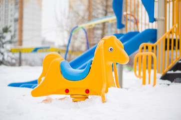 Swing horse and slides on back on winter playground