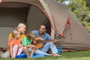 Father playing guitar for family on camping holiday