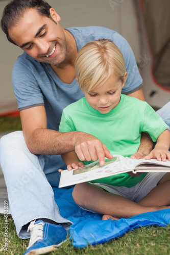 Father helping son to read at the campsite