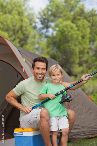 Portrait of father and son holding fishing rod