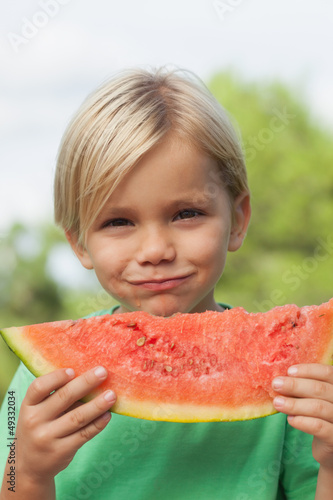 Cute smiling boy eating watermelon