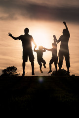Family jumping together at sunset