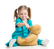 Adorable girl with clothes of doctor spoon feeding plush toy