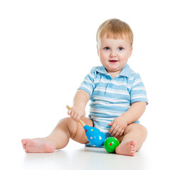 Baby  boy playing with musical toys. Isolated on white backgroun
