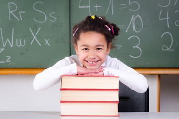 lächelndes kind stützt sich auf büchern ab