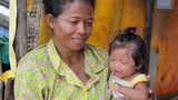 Mother holding baby in cambodian shanty, close dumping area