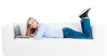 studentin liegt lässig mit dem laptop auf dem sofa