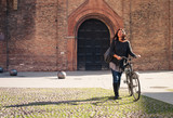Woman walking with bicycle in Saint Stephen square, Bologna, Ita