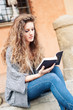 Teenager reading a book in Saint Stephen square, Bologna, Italy.