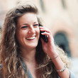Teenager laughing at mobile phone in Saint Stephen square, Bolog