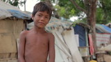 Cambodian boys in slum, shacks at background