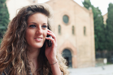 Teenager talking at mobile phone in Saint Stephen square, Bologn