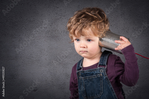 Young kid listen to tin can telephone over grunge background.