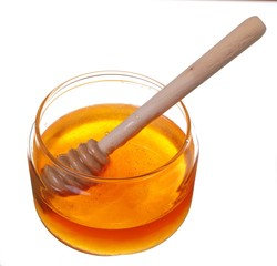 Jar of honey with wooden drizzler isolated on white background
