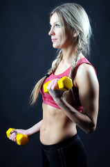 woman lifting dumbbells on dark background