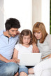 couple with daughter and laptop on sofa