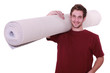 Young man with a roll of carpet