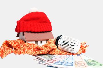 Thermostat mit Geldscheinen und kleinem Haus