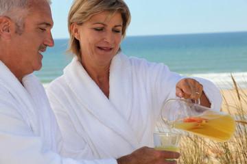 Mature couple drinking on beach
