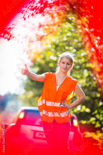 Young female driver wearing a high visibility vest/safety vest,