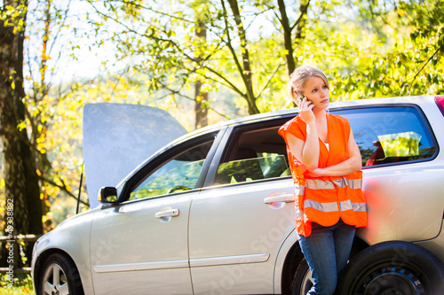 Young female driver calling the roadside service