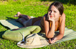 Woman in swimsuit is lying on green grass near the sea
