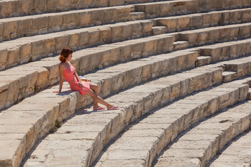 Girl is sitting on the steps of amphitheater