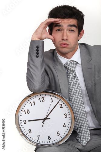 Business with clock suffering from headache
