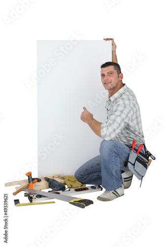 Carpenter posing by advertising panel