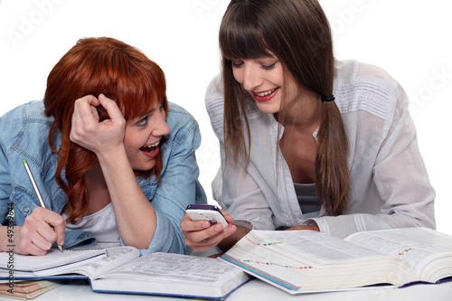 two girlfriends studying and having fun together