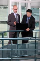Businessmen standing in a corridor with laptop