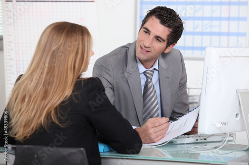 Man interviewing a young woman across a desk