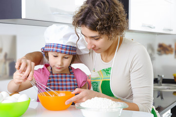 Young mother with little daughter preparing cookies