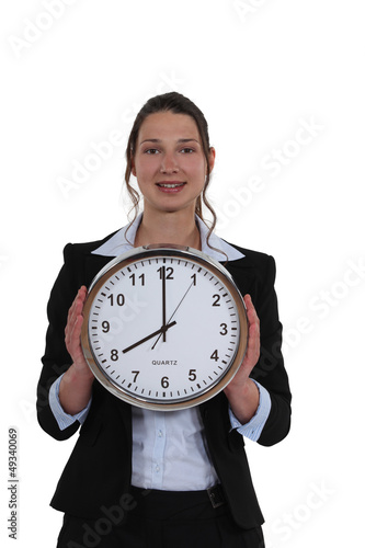 woman in a suit holding a huge clock