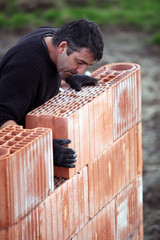 A tradesman laying a brick